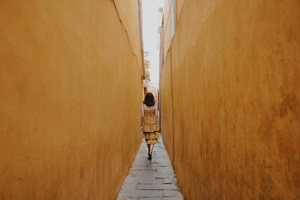 woman walking through yellow walls- coaching for women at the happy space
